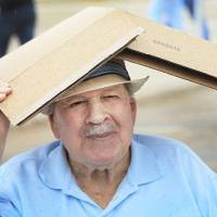 Photo - Perry Sanders, 90, uses a box to keep the rain off his head on a trip on Senior Citizen's Day to the 2011 Oklahoma State Fair, Wednesday, September 21, 2011.  Sanders was with a group from Meadowlake  Estates in south Oklahoma City. Photo by David McDaniel, The Oklahoman