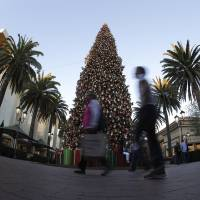 Photo - In this Thursday, Dec. 20, 2012, photo,  holiday shoppers walk past a large Christmas tree at Fashion Island shopping center in Newport Beach, Calif. U.S. consumers increased their spending at retail businesses in December, buying more autos, furniture and clothing. (AP Photo/Chris Carlson)