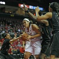 Photo - Maryland's Brionna Jones, center, drives to the basket as Florida State's Cheetah Delgado, left, Natasha Howard, center right, and Morgan Jones defend in the first half of an NCAA college basketball game Thursday, Feb. 20, 2014, in College Park, Md. (AP Photo/Gail Burton)