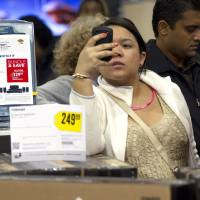Photo - FILE - In this Thursday, Nov. 22, 2012, file photo a shopper uses her smart phone at the Pembroke Pines, Fla. Best Buy. Facebook isn't just for goofy pictures and silly chatter. Whether shoppers know it or not, their actions online help dictate what's in stores during this holiday season. (AP Photo/J Pat Carter, File)
