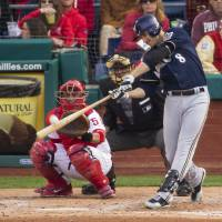 Photo - Milwaukee Brewers' Ryan Braun hits a solo home run in front of Philadelphia Phillies catcher Carlos Ruiz (51) during the fourth inning of a baseball game, Tuesday, April 8, 2014, in Philadelphia. (AP Photo/Chris Szagola)