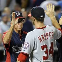 Photo -   FILE - In this July 24, 2012 file photo, Washington Nationals manager Davey Johnson high-fives Bryce Harper (34) after the Nationals defeated the New York Mets in a baseball game, at Citi Field in New York. One's the oldest manager in the majors. The other put together the best season by a teen hitter since the 1960s. Davey Johnson, 69, and Bryce Harper, 19, were born a half-century apart, and they came together to help the Washington Nationals build the best record in baseball in 2012.
