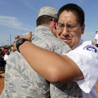 Photo -   Stephen Begay, right, embraces Max Broderick at a memorial ceremony Tuesday in Moore. A resident of the Plaza Towers neighborhood, Broderick helped Begay pull his grandmother from the rubble of her tornado-ravaged home. His grandmother, Kathryn Begay, succumbed to her injuries 73 days later. Photo by Steve Sisney, The Oklahoman   STEVE SISNEY -