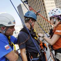 Photo - Volunteer Rich Pumplin, left, and Rebecca Land Segrest, site safety supervisor for Over the Edge, check the equipment on The Oklahoman's Jonathan Sutton before he rappels off the 16th floor of Leadership Square during a media opportunity with the Girl Scouts of Western Oklahoma in Oklahoma City, Friday, Aug. 22, 2014. The Girls Scouts are raising money for a storm shelter at one of their camps. Anyone who raises $1000 or more has the opportunity to rappel down Leadership Square on Saturday. Photo by Nate Billings, The Oklahoman