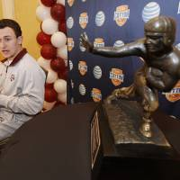 Photo - CORRECTS YEAR - Texas A&M freshman quarterback Johnny Manziel answer questions during a Cotton Bowl press conference, with a Heisman Trophy at side, at the Omni Mandalay hotel, Tuesday, Jan. 1, 2013, in Irving, Texas. Texas A&M plays Oklahoma on Jan. 4 in the Cotton Bowl in Arlington, Texas. (AP Photo/Brandon Wade)