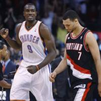 Photo - Oklahoma City Thunder forward Serge Ibaka, left, of Republic of Congo, pumps his fist as Portland Trail Blazers guard Brandon Roy, right, walks off the court, at the end of an NBA basketball game in Oklahoma City, Friday, Nov. 12, 2010. Oklahoma City won 110-108. (AP Photo/Sue Ogrocki) ORG XMIT: OKSO113