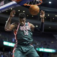 Photo - Milwaukee Bucks forward Jeff Adrien (12) dunks the ball against the Detroit Pistons during the first half of an NBA basketball game Monday, March 31, 2014, in Auburn Hills, Mich. (AP Photo/Duane Burleson)