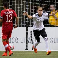 Photo - Germany's Simone Laudehr, right, celebrates her penalty kick goal as Canada's Christine Sinclair looks on during the second half of an international women's soccer game in Vancouver, British Columbia on Wednesday, June 18, 2014.  (AP Photo/The Canadian Press, Darryl Dyck)