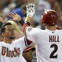 Photo - Arizona Diamondbacks' Aaron Hill (2) gets high-fives from teammate David Peralta after Hill hit a home run against the Detroit Tigers during the first inning of a baseball game on Tuesday, July 22, 2014, in Phoenix. (AP Photo)