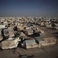 Photo - This Wednesday, Oct. 23, 2013, photo shows a general view of Zaatari refugee camp near the Syrian border in Jordan. With Syria's civil war in its third year, more than 2 million Syrians have fled their country. About 100,000 live in this camp. (AP Photo/Manu Brabo)