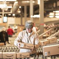Photo - An Amazon.com employee grabs boxes off a conveyor belt to load in a truck at a warehouse in Fernley, Nev. AP Photo  Scott Sady