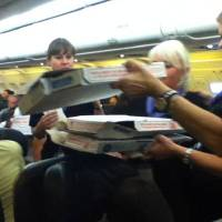 Photo - In this photo taken Monday, July 7, 2014, a Frontier Airlines flight attendant passes out pizza to passengers aboard a Denver-bound flight diverted to Cheyenne, Wyo. The airplane pilot treated his passengers to the pizza after they were diverted. (AP Photo/Logan Marie Torres)