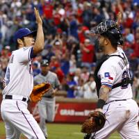 Photo -   Texas Rangers relief pitcher Koji Uehara, left, celebrates with catcher Mike Napoli (25) after beating the Seattle Mariners 2-1 in a baseball game Sunday, Sep. 16, 2012, in Arlington, Texas. (AP Photo/Jim Cowsert)
