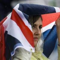 Photo -   A spectator covers her head from the rain with a British flag during the equestrian eventing dressage phase at Greenwich Park, at the 2012 Summer Olympics, Sunday, July 29, 2012, in London. (AP Photo/Markus Schreiber)
