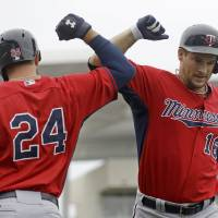 Photo - Minnesota Twins' Josh Willingham (16) is greeted by Trevor Plouffe (24) after hitting a solo home run during the second inning of an exhibition baseball game against the Boston Red Sox in Fort Myers, Fla., Saturday, March 29, 2014. (AP Photo/Gerald Herbert)