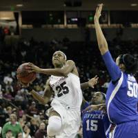 Photo - South Carolina's Tiffany Mithchell (25) drives for the basket as Kentucky's Linnae Harper (15) and Azia Bishop (50) tries to block during the first half of their NCAA college basketball game, Thursday Jan. 9, 2014, in Columbia, S.C. (AP Photo/Mary Ann Chastain)