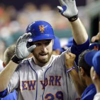 Photo - New York Mets' Ike Davis celebrates his two-run home run with his teammates during the fourth inning of a baseball game against the Washington Nationals at Nationals Park, Friday, Aug. 30, 2013, in Washington. (AP Photo/Alex Brandon)