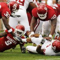 Photo - Javon Harris (30), Gabe Lynn (9) and Jordan Phillips (80) bring down Brennan Clay (24) during the University of Oklahoma (OU) football team's annual Red and White Game at Gaylord Family/Oklahoma Memorial Stadium on Saturday, April 14, 2012, in Norman, Okla.  Photo by Steve Sisney, The Oklahoman