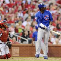 Photo - Chicago Cubs' Junior Lake, right, watches his three-run home run as St. Louis Cardinals' Yadier Molina, left, looks on in the second inning in a baseball game, Monday, May 12, 2014, at Busch Stadium in St. Louis. (AP Photo/Bill Boyce)