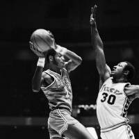 Photo - The Buffalo Braves' Bob McAdoo, left, goes to the hoop against Philadelphia's George McGinnis, right, in 1976. AP photo
