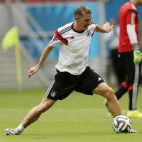 Photo - Germany's Bastian Schweinsteiger works out during a training session in Recife, Brazil, Wednesday, June 25, 2014. Germany will play the United States in group G of the 2014 soccer World Cup on June 26. (AP Photo/Julio Cortez)
