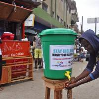 Photo - A man washes his hands in a attempt to stop the spread of the deadly Ebola virus in the city of Monrovia, Liberia, Wednesday, Aug. 6, 2014.  The World Health Organization has begun an emergency meeting on the Ebola crisis, and said at least 932 deaths in four African countries are blamed on the virus, with many hundreds more being treated in quarantine conditions. (AP Photo/Abbas Dulleh)