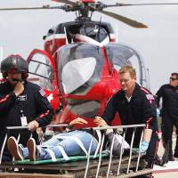 Photo - Life Flight personnel rush a victim wounded in a stabbing attack on the Lone Star community college system's Cypress, Texas campus into Memorial Hermann Hospital Tuesday, April 9, 2013, in Houston. The Harris County Sheriff's department confirmed at least 11 people wounded and that authorities have one suspect in custody. (AP Photo/Houston Chronicle, Johnny Hanson)