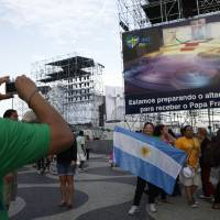Photo - Argentinian pilgrims  takes pictutres in Rio de Janeiro Sunday July 21, 2013, with a giant television monitor erected for the papal visit in the background.    Pope Francis arrives July 22 in  Rio de Janeiro for the World Youth Day.(AP Photo/Jorge Saenz)
