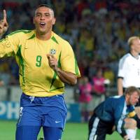 Photo - FILE - In this June 30, 2002,  file photo, Brazil's Ronaldo reacts after scoring past Germany's goalkeeper Oliver Kahn, center, and Carsten Ramelow during their 2002 World Cup final soccer match, at the Yokohama stadium in Yokohama, Japan. On this day: Brazil wins its fifth World Cup as Ronaldo strikes twice to defeat Germany 2-0. (AP Photo/Dusan Vranic, File)