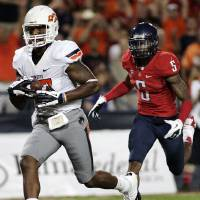 Photo -   Oklahoma States' Tracy Moore (87) outruns Arizona's Shaguille Richardson (5) for a touchdown during the first half of an NCAA college football game at Arizona Stadium in Tucson, Ariz., Saturday, Sept. 8, 2012. (AP Photo/John Miller)
