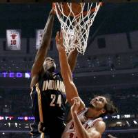 Photo - Indiana Pacers forward Paul George (24) dunks over Chicago Bulls center Joakim Noah (13) during the first half of an NBA basketball game Tuesday, Dec. 4, 2012, in Chicago. (AP Photo/Charles Rex Arbogast)