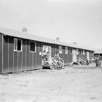 Photo - FILE - In this file photo taken Sept. 21, 1942, relocated Japanese-Americans sit on small front porches on barracks at Rohwer Relocation Center near Rohwer, Ark. The National Park Service on Thursday, June 12, 2014, awarded nearly a quarter-million dollars in grants to projects in Arkansas that help preserve and interpret sites that were used to confine Japanese Americans during World War II. (AP Photo/Horace Cort, File)