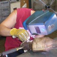 Photo - Welder Travis Filby repairs a stainless steel part at Custom Metal Works Inc. in Tulsa. PHOTO PROVIDED