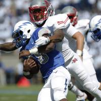 Photo - Nicholls State defensive back Toren Joseph, back, wraps up Air Force running back Jacobi Owens as he carries the ball in the third quarter of an NCAA college football game at Air Force Academy, Colo., on Saturday, Aug. 30, 2014. (AP Photo/David Zalubowski)