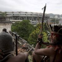 Photo - A man wearing a headdress and another wearing a ski mask sit on a windowsill on the site of an old Indian museum, in Rio de Janeiro, Brazil, Saturday, Jan. 12, 2013. Police in riot gear on Saturday surrounded the site, now an indigenous settlement of men and women living in 10 homes, and prepared to enforce their eviction. The settlement is next to the Maracana stadium, pictured in background, which is being refurbished to host the opening and closing ceremonies of the 2016 Olympics and the final match of the 2014 World Cup. The streets around the stadium will also undergo a vast transformation as part of the area's transformation into a shopping and sports entertainment hub. (AP Photo/Felipe Dana)