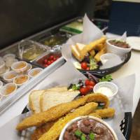 Photo - A basket of Southern fried catfish with a cup of red beans and rice being prepared in the kitchen at the Bayou Grill and Bakery in Edmond Friday.  PAUL B. SOUTHERLAND - THE OKLAHOMAN
