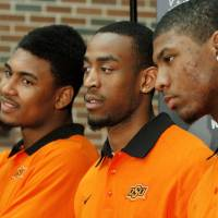 Photo - OSU basketball players, from left,  Le'Bryan Nash, Markel Brown and Marcus Smart delighted  fans when they announced at a noontime press conference they intend to return for another season as members of the Cowboys basketball team. Cheering fans lined all levels in the Student Union atrium Wednesday, April 17, 2013.    by Jim Beckel, The Oklahoman.