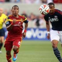 Photo - Real Salt Lake forward Joao Plata (8) and New England Revolution defender Darrius Barnes (25) chase after a loose ball in the first half of an MLS soccer match, Friday, July 4, 2014, in Sandy, Utah. Real Salt Lake won 2-1.(AP Photo/Kim Raff)