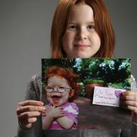 Photo - Ella Turner, 8, holds a photo of her 2-year-old sister, Colby, who died from a disease that affected her heart. Ella is raising money for the American Heart Association.