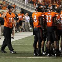 Photo - Oklahoma State's Wes Lunt (11) walks to the OSU huddle during a college football game between Oklahoma State University (OSU) and the University of Texas (UT) at Boone Pickens Stadium in Stillwater, Okla., Saturday, Sept. 29, 2012. Photo by Sarah Phipps, The Oklahoman