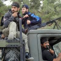 Photo -   In this Sunday October 7, 2012 citizen journalism image provided by Edlib News Network, ENN, which has been authenticated based on its contents and other AP reporting, Free Syrian Army fighters sit on top of a military truck that was captured from the Syrian Army in the village off Khirbet al-Jouz, in the northern province of Idlib, Syria. The Turkish state-run Anadolu news agency said Sunday that the rebels had regained full control of Khirbet al-Jouz. (AP Photo/Edlib News Network ENN)