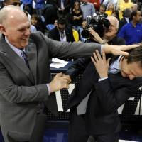 Photo - Denver Nuggets head coach George Karl, left, jokes with Oklahoma City Thunder head coach Scott Brooks before the start of game 4 of a first-round NBA basketball playoff series Monday, April 25, 2011, in Denver. (AP Photo/Jack Dempsey)