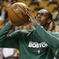 Photo - Injured Boston Celtics point guard Rajon Rondo shoots baskets before Game 3 of a first-round NBA basketball playoff series against the New York Knicks in Boston, Friday, April 26, 2013. (AP Photo/Winslow Townson)