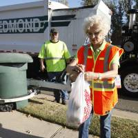 Photo - Edmond sanitation truck driver Jeff Whitfield watches former Mayor Saundra Naifeh, president of Edmond Beautiful, tie a bag of trash. PHOTO BY PAUL HELLSTERN, THE OKLAHOMAN.  PAUL HELLSTERN - Oklahoman