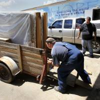 Photo - Brian Dillon, whose home was destroyed by a tornado in May, tornado, loads new furniture into a trailer at a