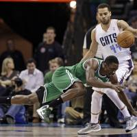 Photo - Boston Celtics' Jeff Green, front, falls as he is fouled by Charlotte Bobcats' Jeffery Taylor, rear, during the first half of an NBA basketball game in Charlotte, N.C., Monday, Feb. 11, 2013. (AP Photo/Chuck Burton)