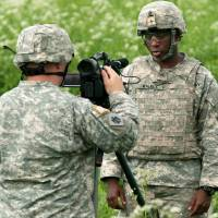 Photo -  Staff Sgt. Christopher Bruce, left, of Harrah, interviews a soldier about his training mission in Tapa, Estonia, on June 10.  Photo by Sgt. Anthony Jones, Oklahoma Army National Guard   Sgt. Anthony Jones -
