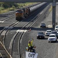 Photo - Abby Brockway waves to supporters from atop a tripod erected on train tracks as an oil train sits idled behind Tuesday, Sept. 2, 2014, in Everett, Wash. About a dozen demonstrators blocked the tracks at a Burlington Northern Santa Fe yard to protest oil and coal export terminals in the Northwest. (AP Photo/Elaine Thompson)