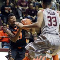 Photo - Oklahoma State guard Marcus Smart (33) looks for a route around Virginia Tech forward Marshall Wood (33) during the second half of an NCAA college basketball game in Blacksburg, Va., Saturday, Dec. 1, 2012. (AP Photo/Daniel Lin) ORG XMIT: VADL112