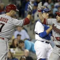 Photo - Arizona Diamondbacks' Miguel Montero, right, celebrates his home run past Los Angeles Dodgers catcher Tim Federowicz with Cody Ross during sixth inning of a baseball game in Los Angeles, Friday, April 18, 2014. (AP Photo/Chris Carlson)